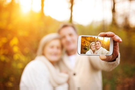 old couple walking: Active seniors taking selfies of them having fun outside in the autumn forest