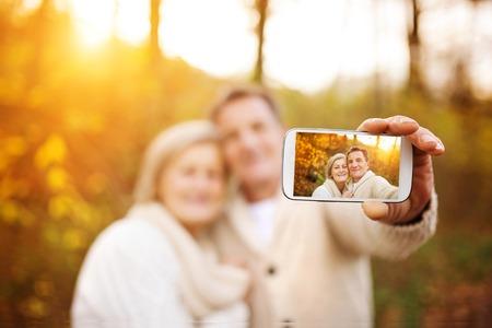 an elderly person: Mayores activos que toman selfies de ellos fuera de la diversi�n en el bosque de oto�o Foto de archivo