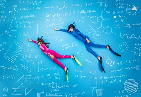 young boy in pool: Children scuba diving in between math formula. Studio shot on a blue background.