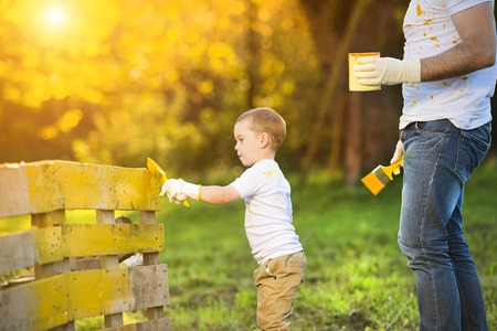 Cute little boy and his father painting wooden fence together on sunny day in nature photo