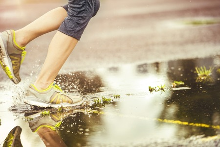 girl in rain: Young woman jogging on asphalt in rainy weather
