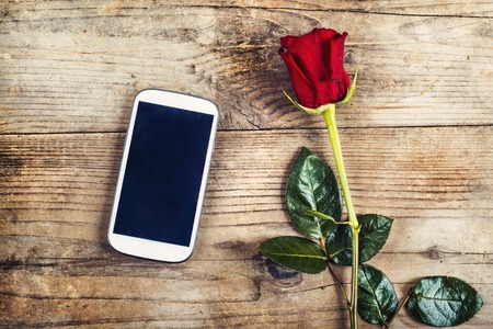 Valentines day composition of yet not written love message in a phone and a red rose. Studio shot on a wooden floor backround. photo