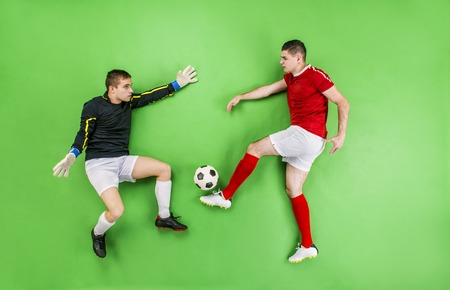 Goalkeeper catching a ball that football player kicks. Studio shot on a green background. photo