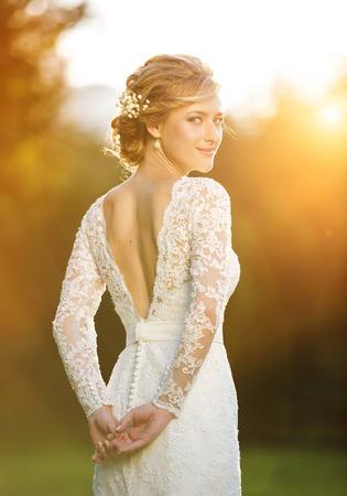 Gelukkig mooie jonge bruid buiten op een zomer weide bij de zonsondergang