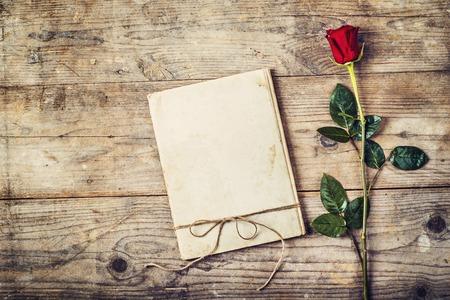 uomo rosso: Valentines composizione giorno di una rivista amore e una rosa rossa. Studio girato su un pavimento di legno sfondo. Archivio Fotografico