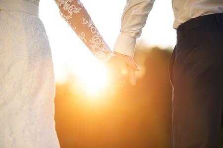 Jonge bruiloft bedrijf paar handen als ze genieten van romantische momenten buiten op een zomer weide