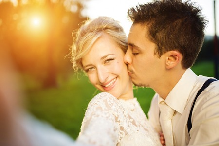 Young wedding couple taking a selfie of themselves as they enjoy romantic moments outside on a summer meadow photo