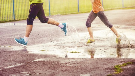 couple exercising: Young couple jogging on asphalt in rainy weather