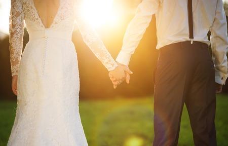 그들은 여름 초원에 밖에 서 로맨틱 한 순간을 즐길 젊은 웨딩 커플 손을 잡고