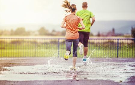 pareja saludable: Pareja trotar joven en el asfalto en tiempo de lluvia