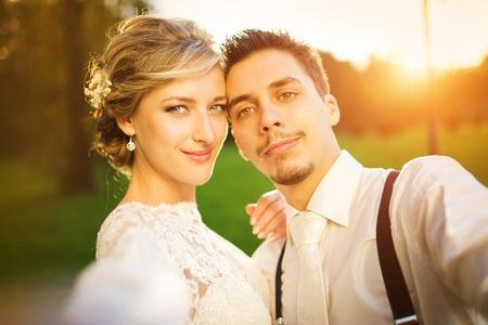 Jonge bruidspaar nemen van een Selfie van zichzelf als ze genieten van romantische momenten buiten op een zomer weide