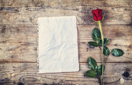 Valentines day composition of rumpled sheet of paper or blank love letter and red rose. Studio shot on a wooden floor background. photo