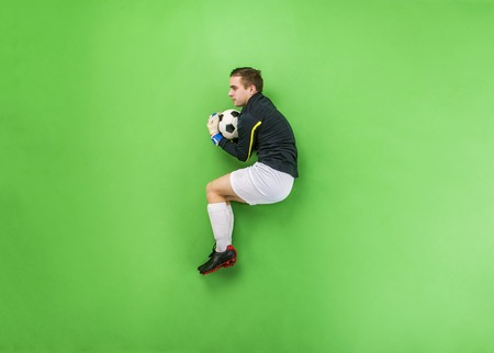 Goalkeeper in action catching a ball. Studio shot on a green background. photo