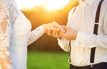 wesele: Młoda para trzymając się za ręce, jak ślub oni cieszyć romantyczne chwile na zewnątrz, na letniej łące