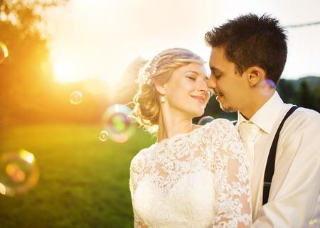 Jonge bruidspaar geniet van romantische momenten buiten in een zomer park.