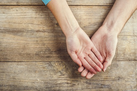 curare teneramente: Mani di uomo e donna insieme. Studio girato su uno sfondo di legno, vista dall'alto. Archivio Fotografico