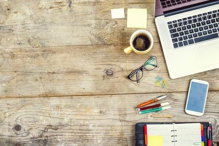Mélanger de fournitures et de gadgets de bureau sur une table de fond en bois. Vue de dessus.