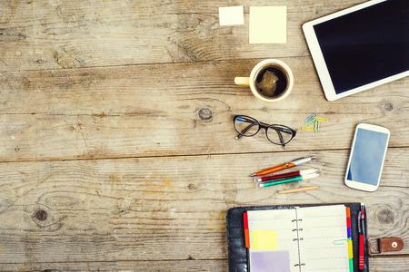 Mix van kantoorbenodigdheden en gadgets op een houten tafel achtergrond. Van bovenaf te bekijken.