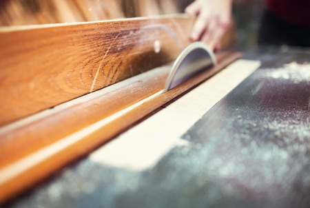 Unrecognizable carpenter cutting wooden planks with table saw photo