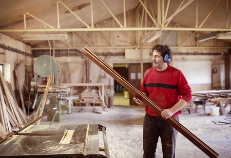 Carpenter cutting wooden planks with table saw photo