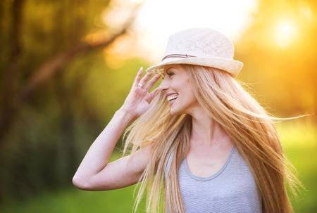 cabello rubio: Atractiva joven disfrutando de su tiempo al aire libre en el parque con la puesta de sol en el fondo. Foto de archivo