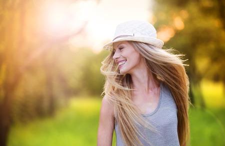 riendo: Atractiva joven disfrutando de su tiempo al aire libre en el parque con la puesta de sol en el fondo. Foto de archivo