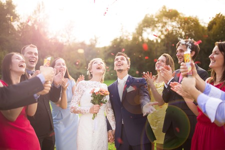 Full length portrait of newlywed couple and their friends at the wedding party showered with confetti in green sunny park Фото со стока