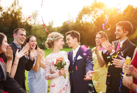 party dress: Full length portrait of newlywed couple and their friends at the wedding party showered with confetti in green sunny park Stock Photo