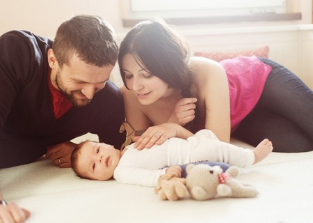 Happy young parents with their little baby girl at home