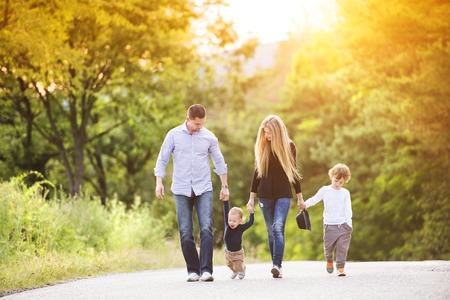 convivencia familiar: Familia de joven feliz caminando por la carretera fuera en la naturaleza verde. Foto de archivo