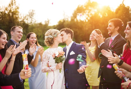 groom: Full length portrait of newlywed couple and their friends at the wedding party showered with confetti in green sunny park Stock Photo