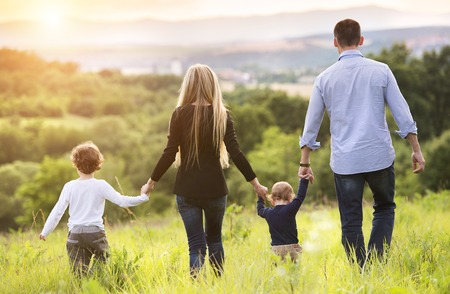 together: Happy young family spending time together outside in green nature. Stock Photo