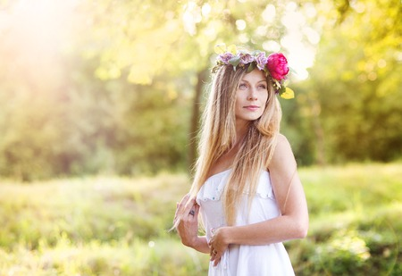 Attractive young woman with flower wreath on her head with sunset in background. photo