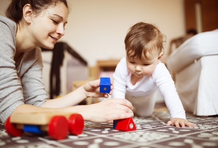 Cute little baby girl playing with her mother on a carpet in a living room.