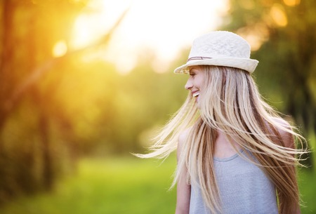vrouwen: Aantrekkelijke jonge vrouw genieten van haar tijd buiten in het park met zonsondergang op de achtergrond.
