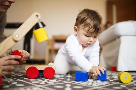 かわいい小さな女の赤ちゃん、リビング ルームのカーペットの上で彼女の母親と一緒に遊んで。