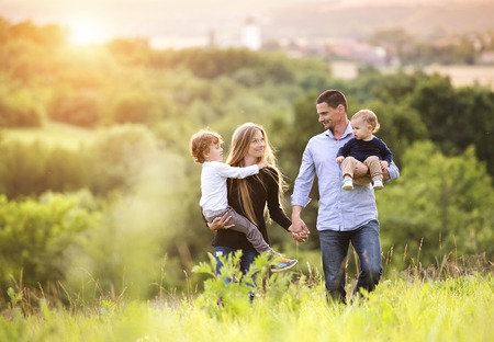 people laughing: Happy young family spending time together outside in green nature. Stock Photo
