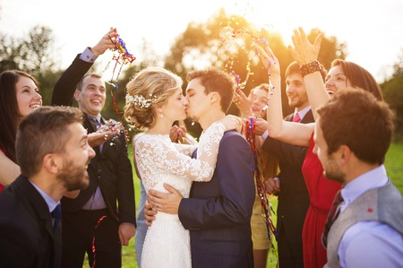 Full length portrait of newlywed couple and their friends at the wedding party showered with confetti in green sunny park photo