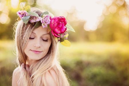 背景の夕日と彼女の頭の上の花の花輪を持つ魅力的な若い女性。
