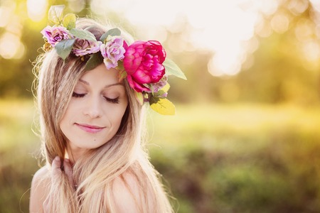 Attractive young woman with flower wreath on her head with sunset in background. Stockfoto