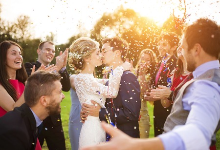 party friends: Full length portrait of newlywed couple and their friends at the wedding party showered with confetti in green sunny park Stock Photo