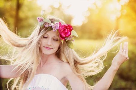 cabello rubio: Mujer joven atractiva con corona de flores en la cabeza con la puesta de sol en el fondo.