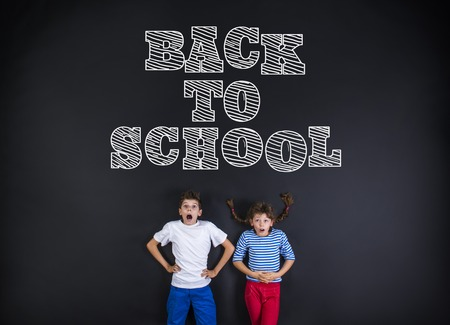 Cute boy and girl standing in frot of a big blackboard. Studio shot on black background. photo