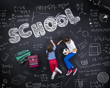 writing board: Cute boy and girl learning playfully in frot of a big blackboard. Studio shot on black background.