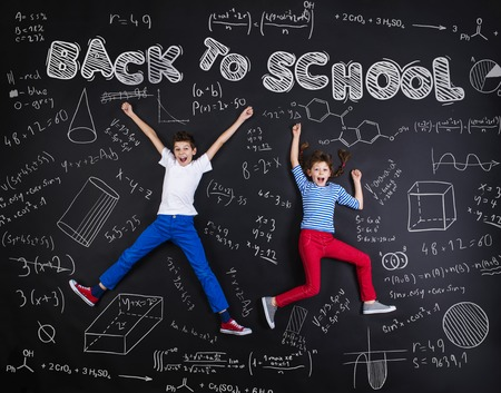 chalk board background: Cute boy and girl learning playfully in frot of a big blackboard. Studio shot on black background.