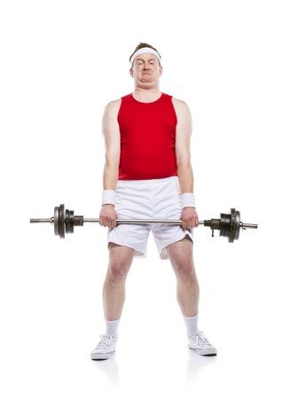 Lustige schwache Bodybuilder versucht, ein Gewicht zu heben. Studio Schuss auf weißem Hintergrund.