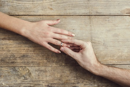 tenderly: Man putting on engagement ring tenderly to his woman. Studio shot on a wooden background, view from above. Stock Photo