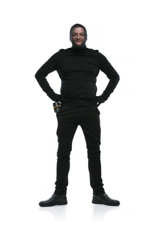 Thief in action with balaclava on his face, dressed in black. Studio shot on white background. photo