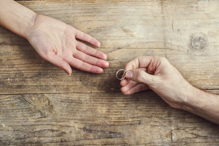 tenderly: Man offering a wedding ring tenderly to a woman. Studio shot on a wooden background, view from above.