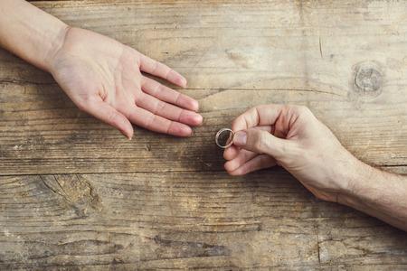 tenderly: Uomo che offre un anello di nozze teneramente a una donna. Studio girato su uno sfondo di legno, vista dall'alto. Archivio Fotografico